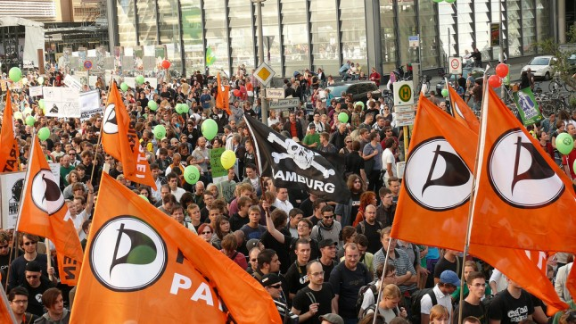 Rally with Piratenpartei flags and a Hamburg flag near center. Photo by Zam_Pano@FlickR, CC license.