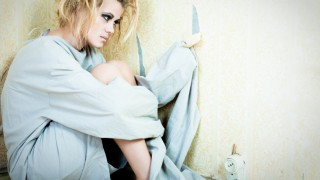 Young adult psycho girl sitting on the floor, blue and green toning