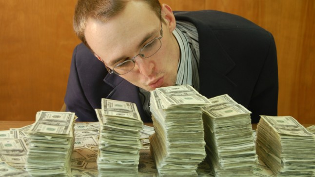 A man kissing his piles of money