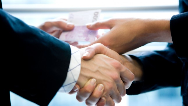Business Handshake. Money changing hands in background.