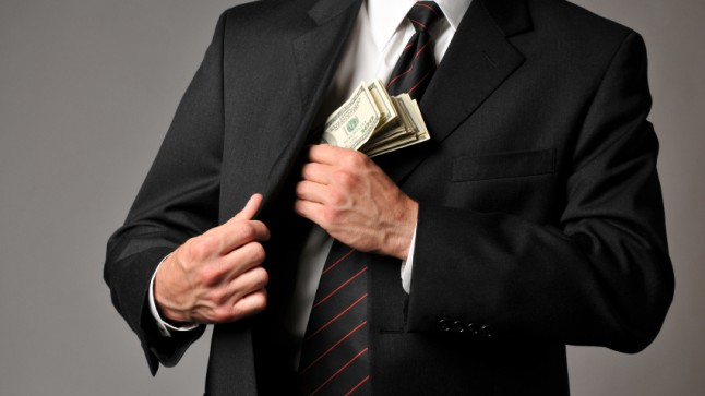 Man in suit pocketing money