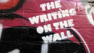 "Stenciled spraypaint on wall saying ""The Writing On The Wall"". Photo by duncan at Flickr, CC-BY-NC."