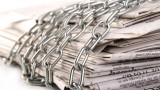 Newspapers (symbolizing newsflow) wrapped in chains