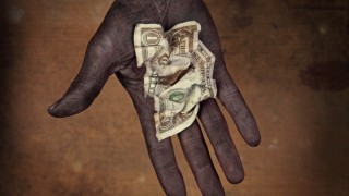 Dark-skinned, possibly malnourished hand holding a crumpled one-dollar note