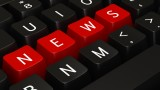 "Close-up of a keyboard with keys rearranged to spell out the word ""news"""