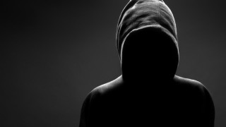 Hooded ominous figure, face invisible in shadows