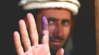 Afghan Voter with purple finger. CC-BY-NC by U.S. Army Garrison - Miami
