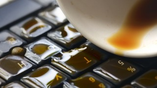 Cup of coffee being poured over keyboard