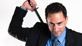 Smiling businessman drawing katana from back