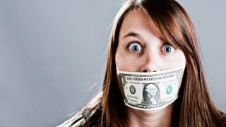 Young woman whose mouth is taped shut by a dollar bill
