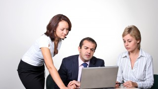 Two people helping a third with something on a laptop