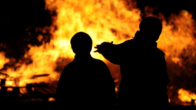 Silhouettes in front of a world on fire