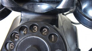 A very old telephone (landline, handset, rotary dial)