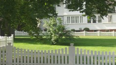 Fences on a lawn, private residence in background, signifying dividers and privacy.