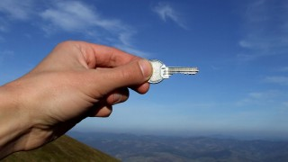 Hand holding key against sky