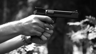 A gun in a man&#039;s hand on a dark background
