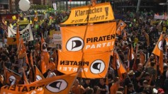 Supporters of German wing of Pirate Party (Piraten Partei) wave their flags during rally against state and corporate surveillance policies in Berlin