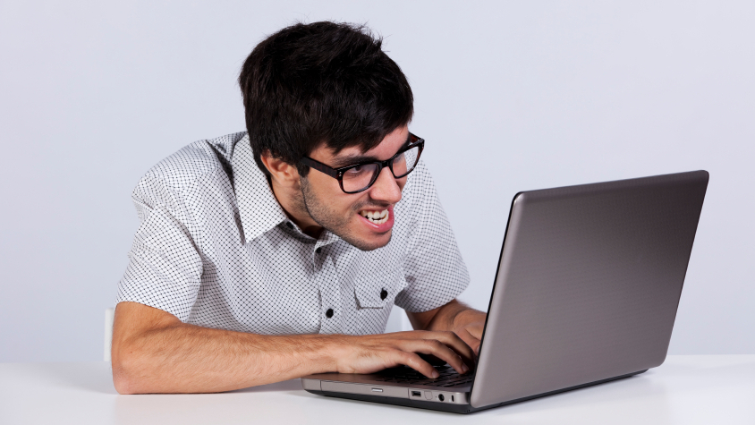 Maniacally lazy guy working fervently on a laptop