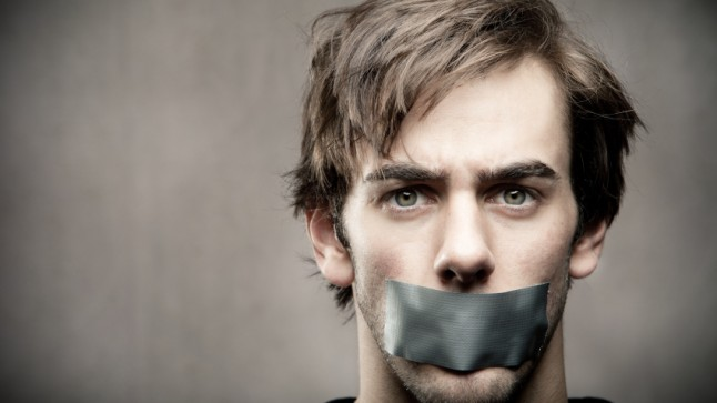 Young annoyed man with duct taped mouth
