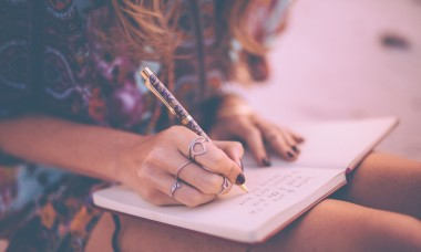 boho-girl-writing-in-her-diary-wearing-a-floral-dress-picture-id472391844