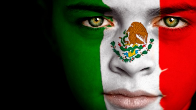Portrait of a concerned boy with the flag of Mexico painted on his face.