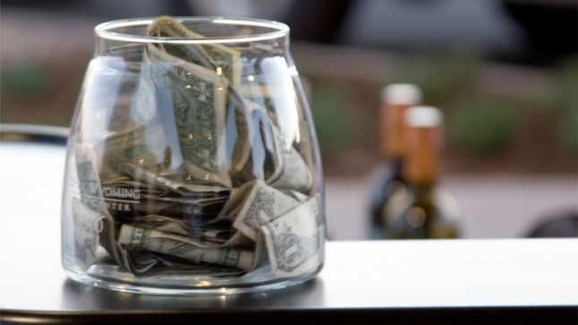 A tip jar filled with cash on a bar. I was too lazy to come up with a better idea for a picture.