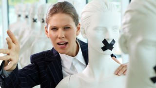 Woman saying something while coming out from behind a mannequin with tape over its mouth