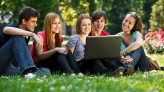 Group of teenagers using laptop outdoors