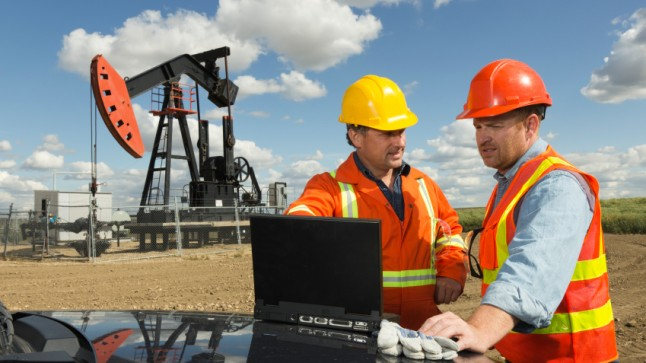Oil company workers with a laptop in the field