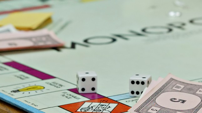 """""""Monopoly"""" board game, dice in foreground"""