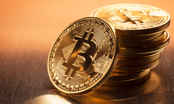 This is a close up photo of several gold plated bitcoins together symbolizing the bit coin market, modern technology, finance, internet, trading, etc.