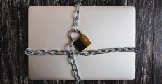 Heavy with a padlock around a laptop isolated on grey table.