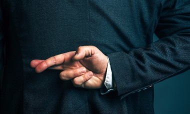 lying-businessman-holding-fingers-crossed-behind-his-back-picture-id533045396